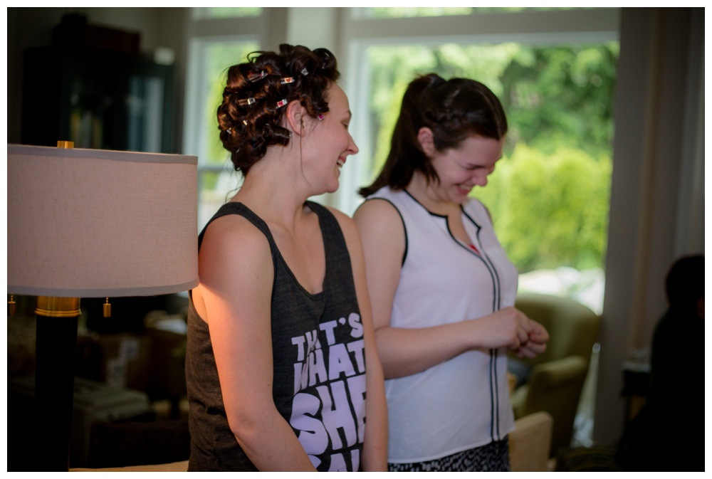 Bride and bridesmaid laughing while getting ready