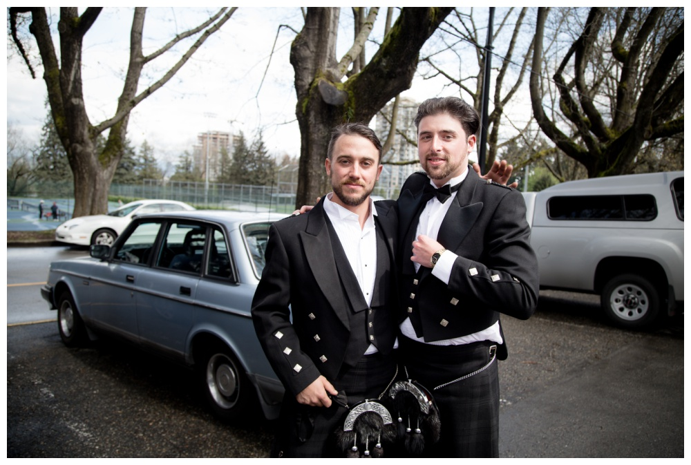 Groom and best man embrace in the parking lot before the ceremony.