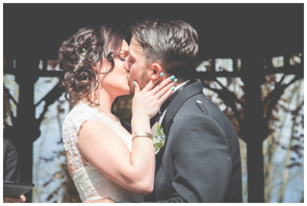Bride pulls groom in for their fist kiss as married couple